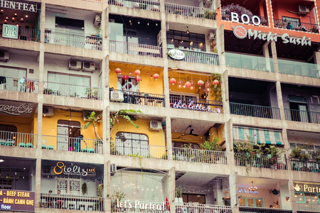 Ho Chi Minh City, Vietnam - November 23, 2018: People rest in cafes located in the old building The Cafe Apartment at the city center.