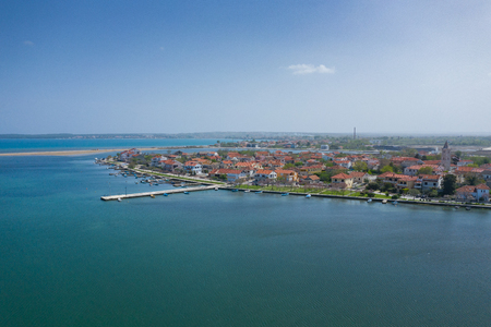 Aerial view of city of Nin. Summer time in Dalmatia region of Croatia. Coastline and turquoise water and blue sky with clouds. Photo made by drone from above.