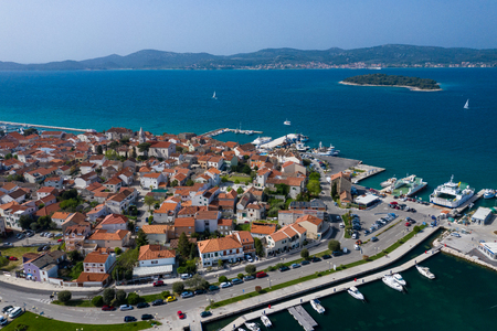 Aerial View of Yacht Club and Marina in Biograd na Moru. Summer time in Dalmatia region of Croatia. Coastline and turquoise water and blue sky. Photo made by drone from above.