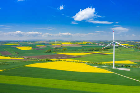 Aerial view of wind turbine. Rapeseed blooming. Windmills and yellow fields from above. Agricultural fields on a summer day. Renewable Energy.
