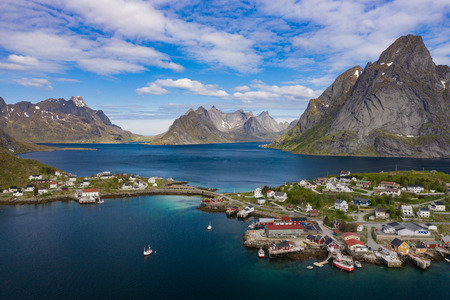 Aerial view of Reine, Lofoten islands, Norway. The fishing village of Reine. Spring time in Nordland. Blue sky. View from above.