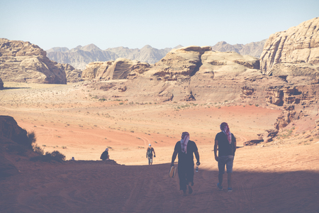 A tourist standing by the look out of a panoramic view of the desert in Wadi Rum, Jordan, Middle East.
