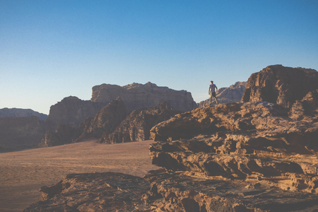 A tourist standing by the look out of a panoramic view of the desert in Wadi Rum, Jordan, Middle East. Standard-Bild - 124316570