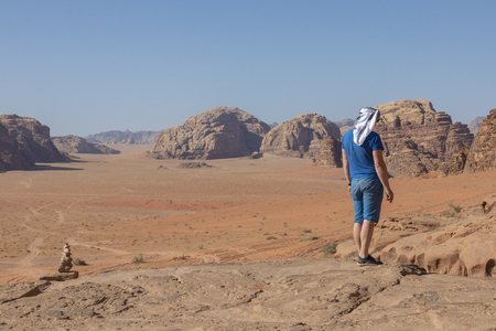 A tourist standing by the look out of a panoramic view of the desert in Wadi Rum, Jordan, Middle East. Standard-Bild - 124316590