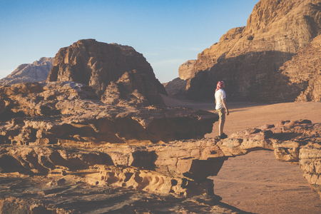 A tourist standing by the look out of a panoramic view of the desert in Wadi Rum, Jordan, Middle East. Standard-Bild - 124316610