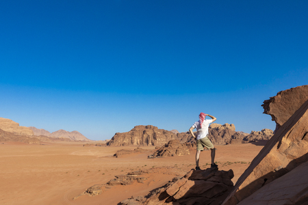 A tourist standing by the look out of a panoramic view of the desert in Wadi Rum, Jordan, Middle East. Standard-Bild - 124316616
