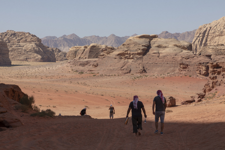 A tourist standing by the look out of a panoramic view of the desert in Wadi Rum, Jordan, Middle East. Standard-Bild - 124316426