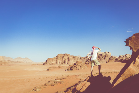 A tourist standing by the look out of a panoramic view of the desert in Wadi Rum, Jordan, Middle East. Standard-Bild - 124316433