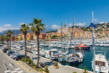 MENTON, FRANCE - JUNE 05, 2019: View of palm tree and harbor with boats in Menton on French Riviera. Provence-Alpes-Cote dAzur, France. Publikacyjne