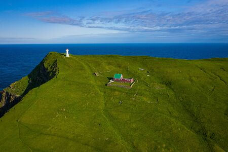 Aerial view of lighthouse at Mykines island in Faroe Islands, North Atlantic Ocean. Photo made by drone from above. Nordic natural landscape.