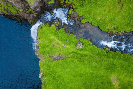 Aerial view of Mulafossur waterfall in Gasadalur village in Faroe Islands, North Atlantic Ocean. Photo made by drone from above. Nordic Natural Landscape.