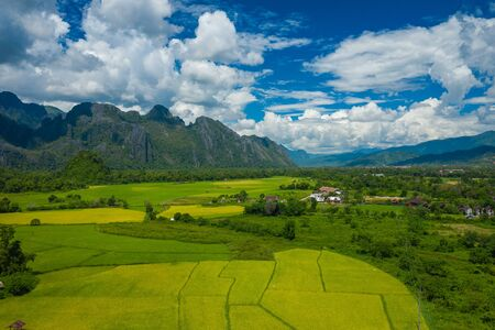 Aerial view of green rice fields and mountains, paddy field at Vang Vieng , Laos. Southeast Asia. Photo made by drone from above. Bird eye view.