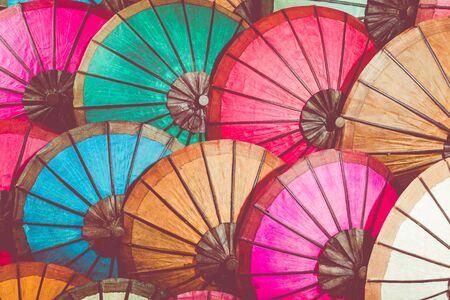 Colorful handmade Asian umbrellas on display at night market in Luang Prabang, Laos.
