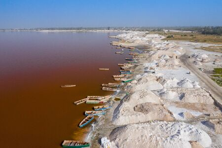 Aerial view of the small boats for salt collecting at pink Lake Retba or Lac Rose in Senegal. Photo made by drone from above. Africa Natural Landscape.
