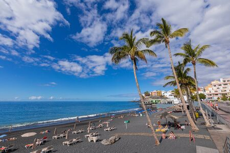 Puerto Naos beach an sunbathing people at beach with black lava sand at La Palma, Canary Island, Spain.