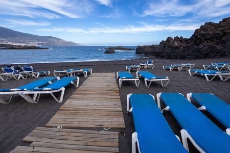 Blue sunbeds and black sand beach at Los Cancajos. La Palma, Canary Island, Spain.