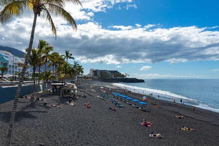 Palms at beach with black lava sand at Puerto Naos in La Palma Island, Canary Island, Spain.