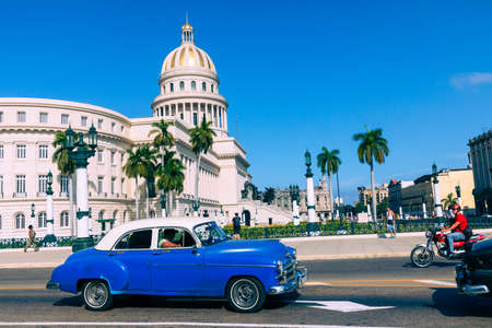 HAVANA, CUBA - DECEMBER 10, 2019: Brightly colored classic American cars serving as taxis pass on the main street in front of the Capitolio building in Central Havana, Cuba. Editorial