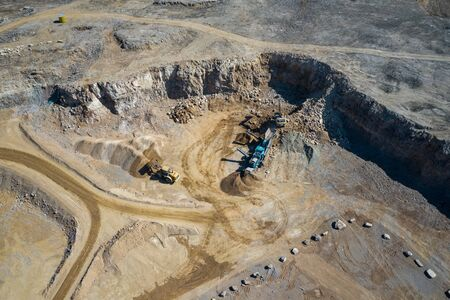 Aerial view of industrial mineral open pit mine. Opencast mining quarry with lots of machinery at work. Drone view from above.