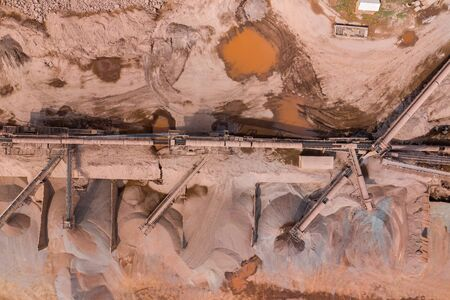 Mining from above. Industrial open pit mineral mine. Aerial view of opencast mining. Mine Excavation. Extractive industry. Giant excavator machinery.