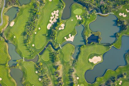 Aerial view of a golf course fairway and green with sand traps, trees and golfers. Reklamní fotografie