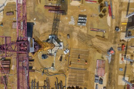 Construction site from above. Aerial view of workplaces in construction equipment, workers with heavy machinery. Industrial top view made by drone.