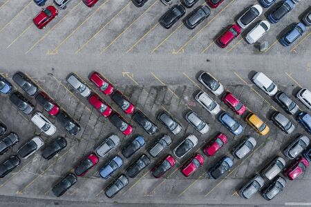 New car lined up aerial view. Port of import and export business logistic to dealership for sale. Automobile and automotive car parking lot for commercial business industry.