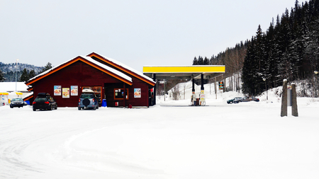 Gas station with a wooden building restaurants. Norwegian winter, late in the afternoon on a cloudy day. Telemark region of Norway