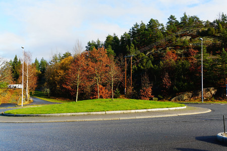 bout: Norwegian roundabout for cars among the trees on a sunny autumn day