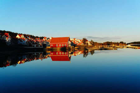 The estate of red wooden cottage on the Norwegian fjord surrounded by water, during an autumn sunset. Mirroring the blue sky and buildings in the water. Telemark region of Norway