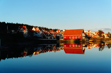 rorbu: Traditional norwegian red rorbu. The estate of red wooden cottage on the Norwegian fjord surrounded by water, during an autumn sunset. Mirroring the blue sky and buildings in the water. Telemark region of Norway Stock Photo