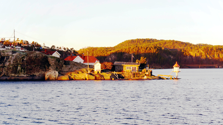 A small lighthouse on the water at the end of the island, on the fjord, Kragero. During sunset. Photo of the ferry. North Sea Coast. Norwegian autumn. Telemark region of Norway photo