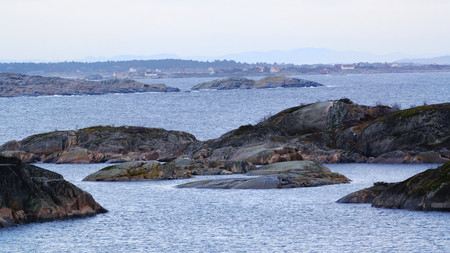 islets: Rocky islets covered with moss. In the distance you can see the houses of fishermen. On the coast of the North Sea. Norwegian autumn. Telemark region of Norway