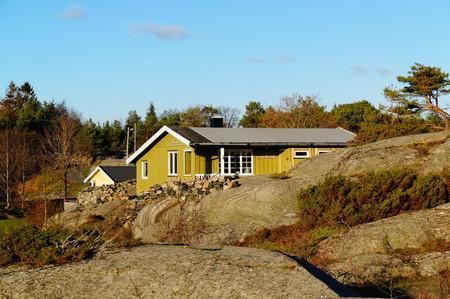 Green cottage hidden between the rocks. North Sea Coast. Norwegian autumn. Telemark region of Norway