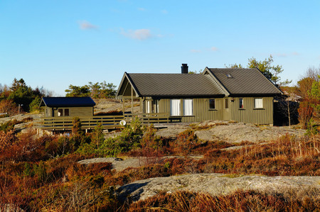 Long-storey cottage with terrace on the rocks. North Sea Coast. Norwegian autumn. Telemark region of Norway Stock Photo