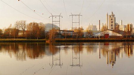 mid distance: Pylons over the water fjord, industrial buildings, autumn day, the city of Porsgrunn, Skien. South Norway. Telemark region of Norway Stock Photo