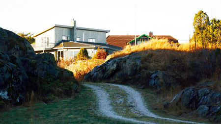 Narrow and winding road with fine white stone, summer cottages, among the rocks. In the shadow. North Sea Coast. Norwegian winter. The sun low on the horizon. Telemark region of Norway