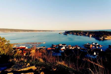 kristiansand: Landscape coast of the sea and the fjord, over the roofs of the wooden houses. In the bottom of an empty dock for boats. North Sea Coast. Norwegian winter. Risor, Aust-Agder region of Ostlandet. Eastern Norway. Stock Photo