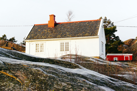lighthouse keeper: Old, traditional wooden building a lighthouse keeper. Painted white walls and old tiles with moss. Wet rocks, covered with ice, frost. North Sea Coast. Norwegian winter. Telemark region of Norway Stock Photo