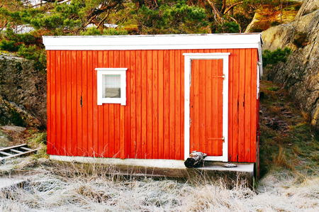 A small red cabin, wooden walls, painted red, small white window. North Sea Coast. Norwegian winter. Telemark region of Norway photo