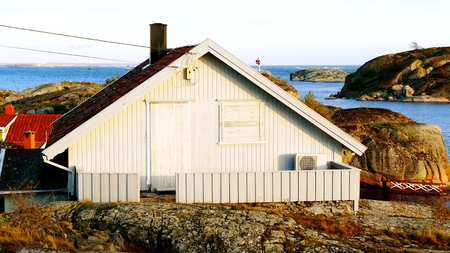 Summer cabin, protected for the winter. Secured windows, secured the door. On the wall air heat pump. North Sea Coast. Norwegian winter. Telemark region of Ostlandet. Eastern Norway. photo