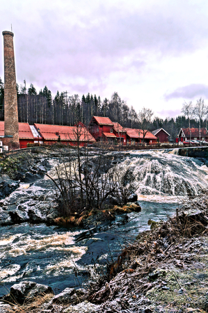 straddle: Old brick buildings foundry, nestled in a narrow valley along the river Lomma. The buildings straddle the river, with several pedestrian bridges connecting them. HDR view. Norwegian winter. Baerum village in Akershus Norway.