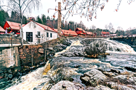straddle: Old brick buildings straddle the river, with several pedestrian bridges connecting them. Foundry, nestled in a narrow valley along the river Lomma.  HDR view. Norwegian winter. Baerum village in Akershus Norway. Stock Photo