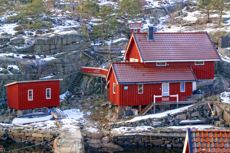 fishing cabin: Red fishing cottages on the bay. High stone walls. Sea north. The sun low on the horizon. In the background of the blue sky. Winter scenery, snow on the rocks. Coniferous forest around. Kragero, Telemark municipality. Region of southeastern Norway. Skager
