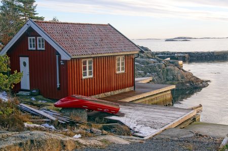next horizon: Fishermans cottage on the bay. Located next to the red boat. Sea north. The sun low on the horizon. In the background of the blue sky. Winter scenery, snow on the rocks. Coniferous forest around. Kragero, Telemark municipality. Region of southeastern Nor