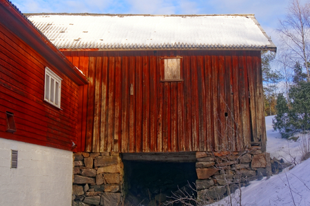 acreage: A large red wooden barn. Snow on the roof of the barn. The sun low on the horizon. In the background of the blue sky. Winter scenery, snow on the rocks. Coniferous forest around. Kragero, Telemark municipality. Region of southeastern Norway. Skagerrak coa