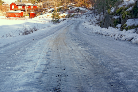 A thick layer of ice on a rocky road. A typical condition of the roads in Norway in winter. Winter scenery, snow on the rocks. Coniferous forest around. Kragero, Telemark municipality. Region of southeastern Norway. Skagerrak coast.