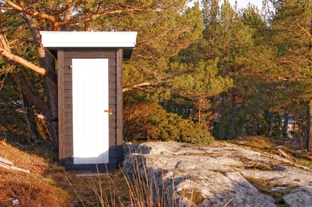 sitting area: Black wooden building toilets. On the rocks of felled pine trees. Sitting area on the coast. Winter scenery, snow on the rocks. Coniferous forest around. Kragero, Telemark municipality. Region of southeastern Norway. Skagerrak coast. Editorial