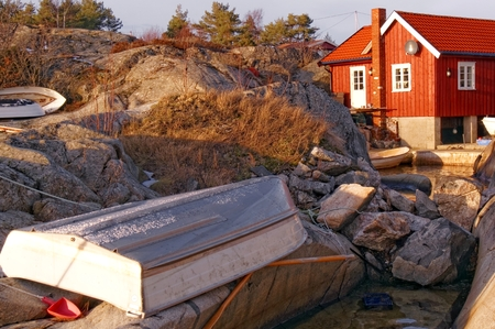 Fishing boat inverted upside down on the rocks. In the background, a red cottage fishing among the rocks. Fishing gear around . Around Winter vegetation and rocks. Vinateg look. Winter scenery, snow on the rocks. Kragero, Telemark municipality. Region of