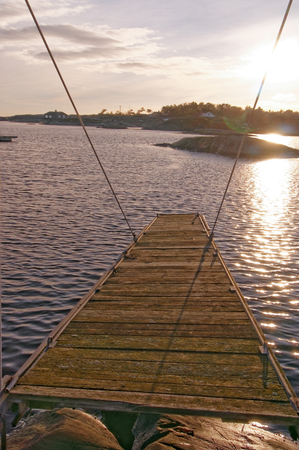 diving platform: Wooden platform for jumping into the water. Wooden bridge overgrown with moss on the fjord. Sunset over the fjord. Around the winter vegetation and rocks. Vintage look. Winter scenery, snow on the rocks. Kragero, Telemark municipality. Region of southeast